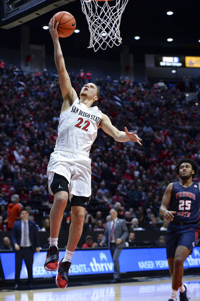 San Diego State guard Malachi Flynn (22) goes to the basket as Fresno State guard Anthony Holland (25) looks on during the second half of an NCAA college basketball game Wednesday, Jan. 1, 2020, in San Diego. San Diego won 61-52. (AP Photo/Orlando Ramirez)