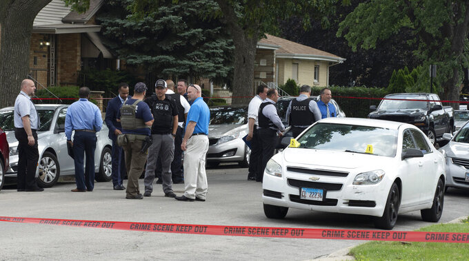 """Chicago Police work on a crime scene in a residential neighborhood, Wednesday, June 7, 2021. Three undercover law enforcement officers were shot and wounded Wednesday morning while driving onto an expressway on Chicago's South Side, and detectives were questioning a """"person of interest"""" about the shooting, police said. The shooting occurred at 5:50 a.m. near the 22nd District police station in the city's Morgan Park neighborhood. (Brian Rich/Chicago Sun-Times via AP)"""