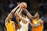 Vanderbilt forward Dylan Disu, center, is defended by Tennessee's Jalen Johnson (13) and Josiah-Jordan James, right, during the first half of an NCAA college basketball game Saturday, Jan. 18, 2020, in Nashville, Tenn. (AP Photo/Mark Humphrey)