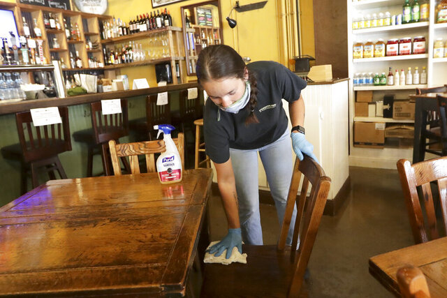 Carlee Packard wipes down a table and chairs after customers finished eating at Puckett's Grocery & Restaurant Monday, April 27, 2020, in Franklin, Tenn. Monday is the first day Tennessee restaurants can reopen with reduced seating and social distancing during the coronavirus pandemic.(AP Photo/Mark Humphrey)