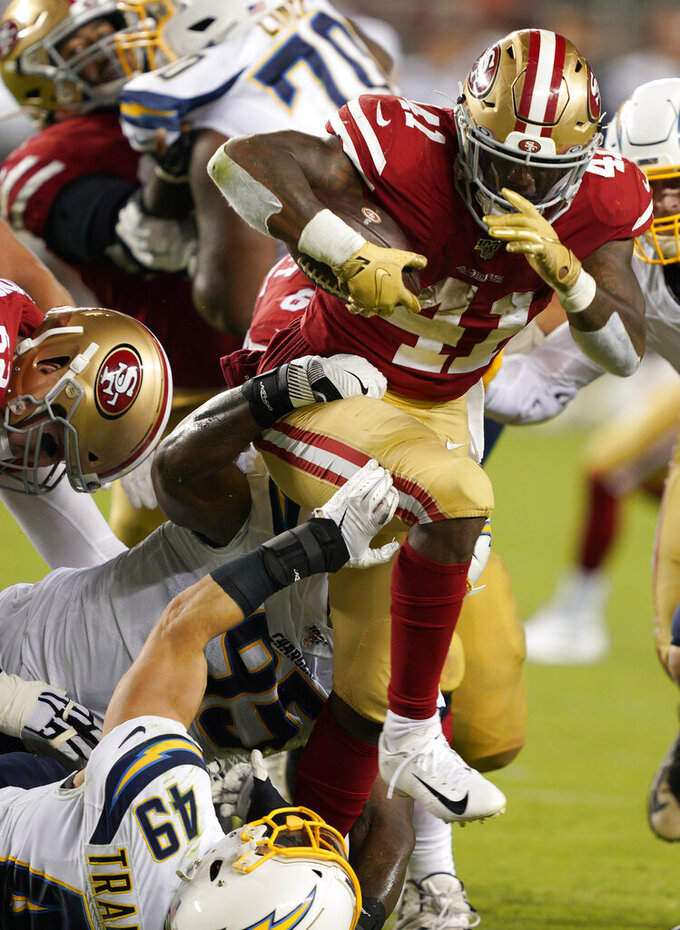 San Francisco 49ers' Jeff Wilson Jr. (41) runs over Los Angeles Chargers' Drue Tranquill (49) during the second half of an NFL preseason football game in Santa Clara, Calif., Thursday, Aug. 29, 2019. (AP Photo/Tony Avelar)