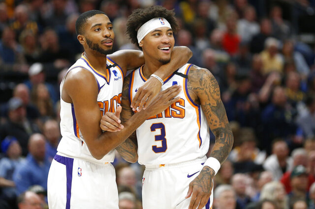 Phoenix Suns forward Mikal Bridges, left, and forward Kelly Oubre Jr. (3) react to a foul called on Oubre in the first half during an NBA basketball game against the Utah Jazz, Monday, Feb. 24, 2020, in Salt Lake City. (AP Photo/Rick Bowmer)