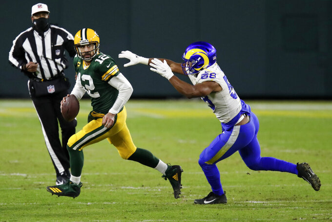 Green Bay Packers quarterback Aaron Rodgers evades Los Angeles Rams' Justin Hollins during the second half of an NFL divisional playoff football game Saturday, Jan. 16, 2021, in Green Bay, Wis. (AP Photo/Matt Ludtke)