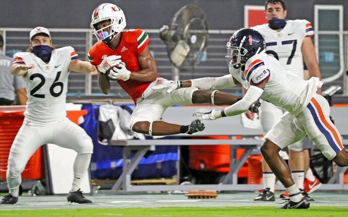 Miami wide receiver Mark Pope (6) catches a first-half pass as Virginia's Nick Grant (1) defends during an NCAA college football game in Miami Gardens, Fla., Saturday, Oct. 24, 2020.   (Al Diaz/Miami Herald via AP)