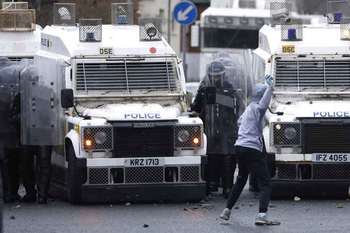 A Nationalist youth prepares to throw a projectile at a police line blocking a road near the Peace Wall in West Belfast, Northern Ireland, Thursday, April 8, 2021. Authorities in Northern Ireland sought to restore calm Thursday after Protestant and Catholic youths in Belfast hurled bricks, fireworks and gasoline bombs at police and each other. It was the worst mayhem in a week of street violence in the region, where Britain's exit from the European Union has unsettled an uneasy political balance. (AP Photo/Peter Morrison)