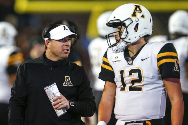 Appalachian State coach Eliah Drinkwitz talks with quarterback Zac Thomas (12) during the second half of the team's NCAA college football game against Troy on Friday, Nov. 29, 2019, in Troy, Ala. (AP Photo/Butch Dill)