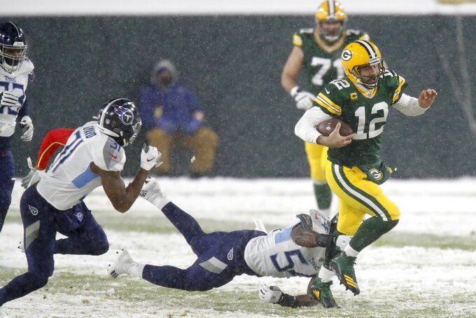 Green Bay Packers' Aaron Rodgers runs for a first down during the first half of an NFL football game against the Tennessee Titans Sunday, Dec. 27, 2020, in Green Bay, Wis. (AP Photo/Matt Ludtke)