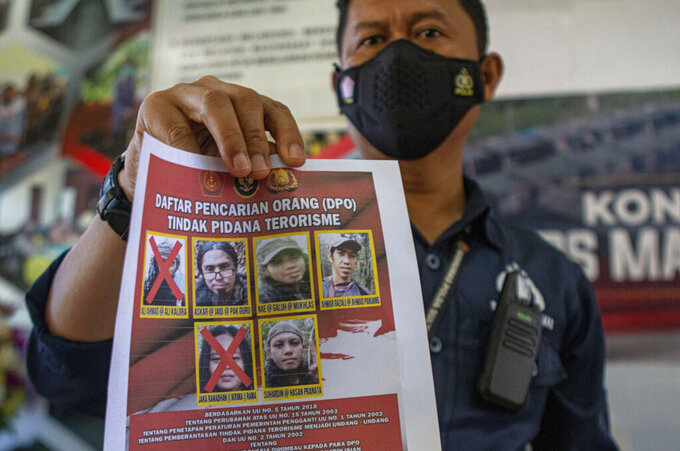 A police officer shows a wanted poster displaying the photos of two militants Ali Kalora, top left, and Jaka Ramadan, bottom left, who were killed during shootout with security forces, during a press conference at the Parigi Moutong Police Station in Parigi Moutong district, Central Sulawesi, Indonesia, Sunday, Sept. 19, 2021. Indonesia's most wanted militant with ties to the Islamic State group was killed Saturday in a shootout with security forces, the Indonesian military said, in a sweeping counterterrorism campaign against extremists in the remote mountain jungles. (AP Photo/Mohammad Taufan)