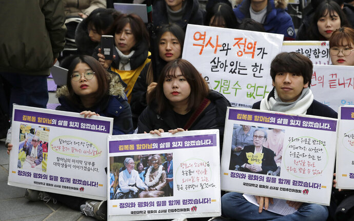 Participants hold pictures of deceased Kim Bok-dong, one of former South Korean sex slaves who were forced to serve for the Japanese military in World War II, during a weekly rally near the Japanese Embassy in Seoul, South Korea, Wednesday, Jan. 30, 2019. Hundreds of South Koreans mourned the death of Kim during the rally demanded reparations from Tokyo over wartime atrocities. The banners read:
