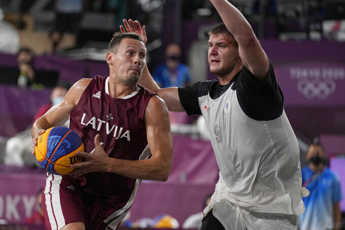Latvia's Agnis Cavars, left, heads to the basket past Ilia Karpenkov (9), of the Russian Olympic Committee, during a men's 3-on-3 gold medal basketball game at the 2020 Summer Olympics, Wednesday, July 28, 2021, in Tokyo, Japan. (AP Photo/Jeff Roberson)