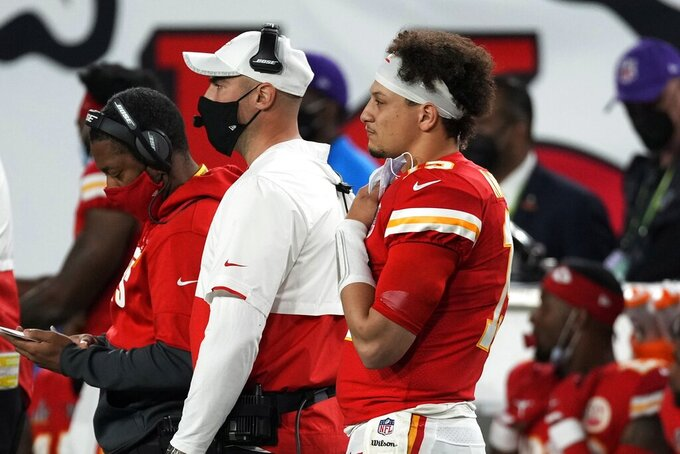 Kansas City Chiefs quarterback Patrick Mahomes, foreground, watches from the bench during the second half of the NFL Super Bowl 55 football game against the Tampa Bay Buccaneers Sunday, Feb. 7, 2021, in Tampa, Fla. (AP Photo/Chris O'Meara)