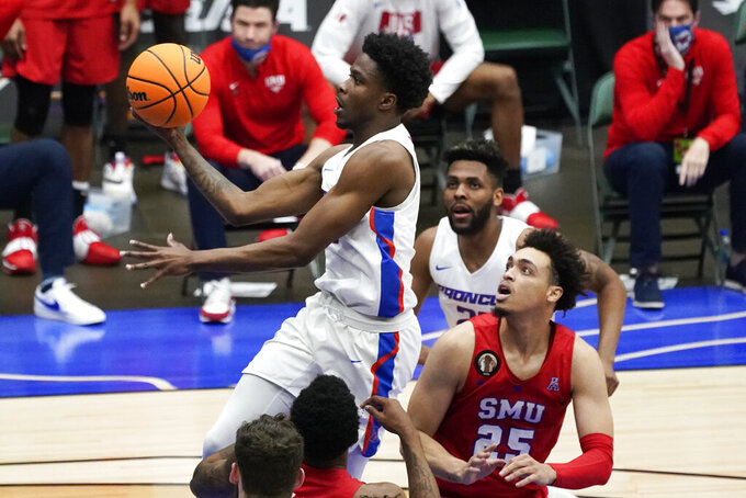 Boise State guard Devonaire Doutrive, left, drives to the basket over SMU forward Ethan Chargois (25) during the first half of an NCAA college basketball game in the first round of the NIT, Thursday, March 18, 2021, in Frisco, Texas. (AP Photo/Tony Gutierrez)