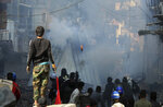 Riot police fire tear gas during clashes with anti-government demonstrators in Baghdad, Iraq, Saturday, Nov. 30, 2019. (AP Photo/Hadi Mizban)