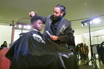 In this Sunday, Feb. 17, 2019 photo, Timaun Norris, 15, gets a haircut from Corvette Derden during