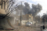 FILE - This file photo provided on Thursday, Feb. 8, 2018 by the Syrian Civil Defense White Helmets, which has been authenticated based on its contents and other AP reporting, shows a plume of smoke while civil defense workers arrive after airstrikes hit a rebel-held suburb near Damascus, Syria. As Syrian troops and their allies push toward final victory and the battle against Islamic State militants draws to an end, new fronts are opening up, threatening an even broader confrontation. The U.S., Israel and Turkey all have deepened their involvement, seeking to protect their interests in the new Syria order. (Syrian Civil Defense White Helmets via AP, File)