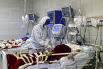 FILE — In this March 1, 2020 file photo, a medic treats a patient infected with coronavirus, at a hospital in Tehran, Iran. Dozens of medical staffers have died of COVID-19 in Iran. Doctors and nurses and other staffers have been hard hit. During the first 90 days of the virus outbreak alone, about one medical staffer died each day. (Ali Shirband/Mizan News Agency via AP, File)