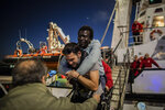 Louis, from Ivory coast, who suffers disability in one leg is helped by David, an aid worker of the Spanish NGO Open Arms, to disembark from the rescue vessel at the port of Messina after being rescued along with other 121 people from different nationalities off the Libyan coast, Sicily, Italy, Wednesday Jan.15, 2020. (AP Photo/Santi Palacios)