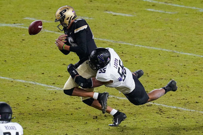 Purdue quarterback Aidan O'Connell (16) fumbles the ball as he's hit by Northwestern defensive lineman Eku Leota (55) during the third quarter of an NCAA college football game in West Lafayette, Ind., Saturday, Nov. 14, 2020. (AP Photo/Michael Conroy)