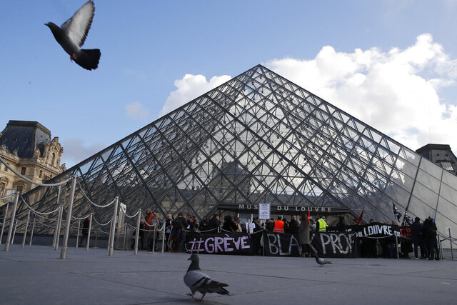 Pigeons fly by the Louvre pyramid as striking employees demonstrate outside the museum Friday, Jan. 17, 2020 in Paris. Paris' Louvre museum was closed Friday as dozens of protesters blocked the entrance to denounce the French government's plans to overhaul the pension system. (AP Photo/Francois Mori)