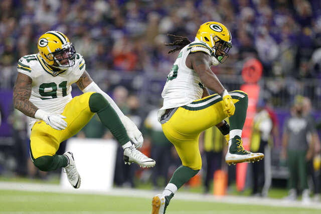 FILE - In this Monday, Dec. 23, 2019, file photo, Green Bay Packers outside linebacker Za'Darius Smith, right, celebrates with teammate Preston Smith after sacking Minnesota Vikings quarterback Kirk Cousins during the second half of an NFL football game in Minneapolis. Za'Darius Smith and Preston Smith aren't related, but the Packers pass rushers share the same last name and the same type of productive games. They combined for 25 ½ sacks last season after both signed with the Packers as free agents in early 2019. (AP Photo/Andy Clayton-King, File)