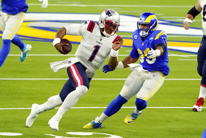New England Patriots quarterback Cam Newton (1) runs past Los Angeles Rams defensive end Aaron Donald during the first half of an NFL football game Thursday, Dec. 10, 2020, in Inglewood, Calif. (AP Photo/Jae C. Hong)
