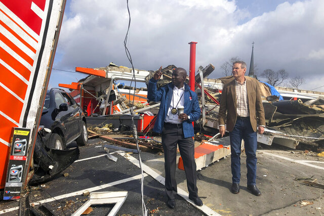Tennessee Gov. Bill Lee, right and Tennessee Commerce and Insurance Commissioner Hodgen Mainda survey storm damage, in Nashville, Tenn. on Tuesday, March 3, 2020. Tornadoes ripped across Tennessee early Tuesday, shredding at least 40 buildings and killing many people. One of the twisters caused severe damage across downtown Nashville and leaving hundreds of people homeless. (AP Photo/Travis Loller)