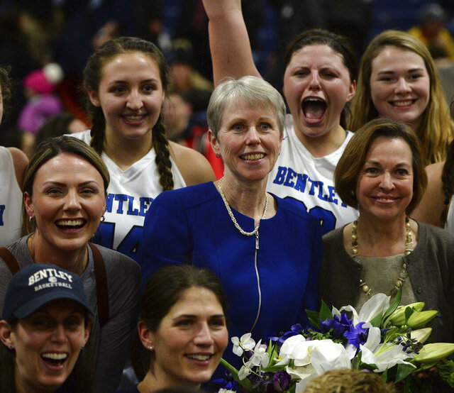 FILE - In this Jan. 17, 2018, file photo, Bentley University women's NCAA college basketball coach Barbara Stevens, center, is congratulated during a team photo after winning her 1000th career game after Bentley beat Adelphi 78-66 in Waltham, Mass. Stevens is retiring after a four-decade run that included more than 1,000 wins, the 2014 NCAA Division II national championship and recent election to the Naismith Memorial Basketball Hall of Fame. (Christopher Evans/The Boston Herald via AP, File)