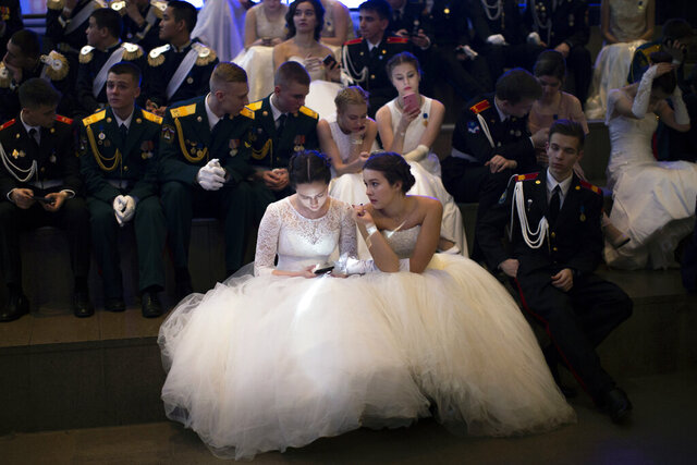 Students of military schools rest after dancing during an annual ball in Moscow, Russia, Tuesday, Dec. 17, 2019. More than 1,000 students from military schools travelled from all over Russia to Moscow to take part in the ball (AP Photo/Alexander Zemlianichenko)