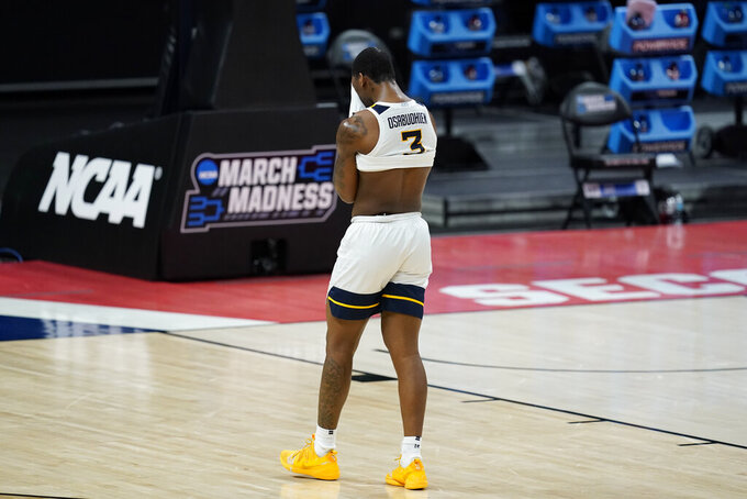 West Virginia's Gabe Osabuohien (3) cover his face as he leaves the court following a second-round game against Syracuse in the NCAA men's college basketball tournament at Bankers Life Fieldhouse, Sunday, March 21, 2021, in Indianapolis. Syracuse defeated Syracuse 75-72. (AP Photo/Darron Cummings)