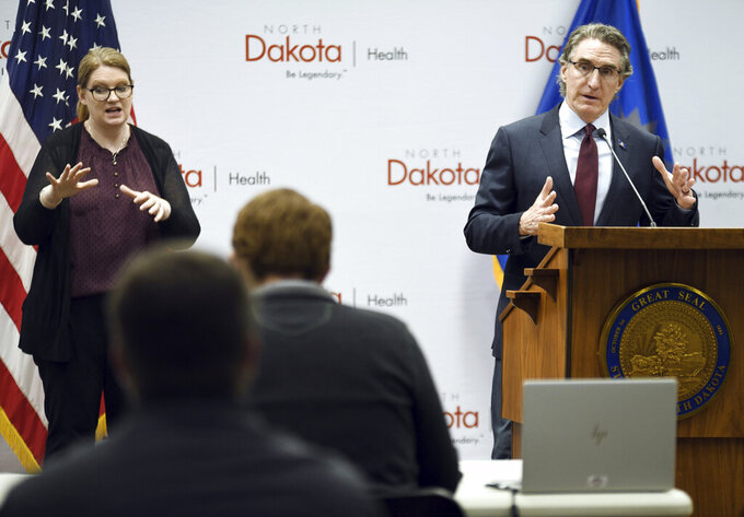 North Dakota Gov. Doug Burgum answers questions during his daily COVID-19 press briefing held at the state Capitol in Bismarck, N.D. Tuesday, April, 7, 2020. On the left is sign language interpreter Lindsey Solberg Herbel. (Mike McCleary/The Bismarck Tribune via AP)