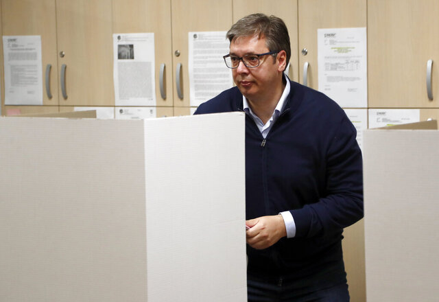 Serbia's President Aleksandar Vucic prepares to vote, at a polling station, in Belgrade, Serbia, Sunday, June 21, 2020. Serbia's ruling populists are set to tighten their hold on power in a Sunday parliamentary election held amid concerns over the spread of the coronavirus in the Balkan country and a partial boycott by the opposition. (AP Photo/Darko Vojinovic)