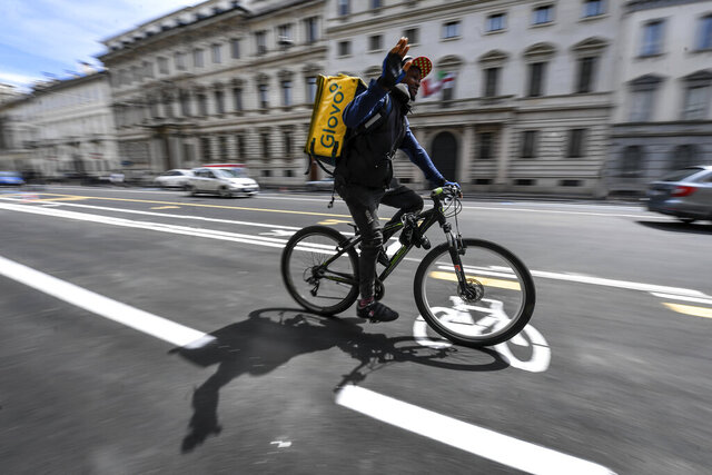 A delivery worker uses the new cycle path being prepared in central Milan's Corso Venezia, Italy, in view of Monday's partial reopening of activities, with a reduced capacity of public transportation due to safety measures against coronavirus, Saturday, May 2, 2020. Italians are preparing for the so called