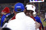 Oklahoma head coach Lincoln Riley, back, and Kansas head coach David Beaty, front, meet mid field following an NCAA college football game in Norman, Okla., Saturday, Nov. 17, 2018. Oklahoma won 55-40. (AP Photo/Alonzo Adams)