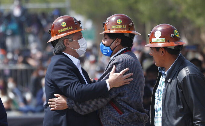 Wearing the work hats of Bolivian miners, Bolivia's former President Evo Morales, center, and Argentina's President Alberto Fernandez, left, embrace as they stand in the middle of the border bridge that connects the town of La Quiaca, Argentina with the town of Villazon, Bolivia, Monday, Nov. 9, 2020. Morales, who fled into exile after resigning last November, returned to his homeland the day after the presidential inauguration of his former finance minister Luis Arce. (AP Photo/Juan Karita)