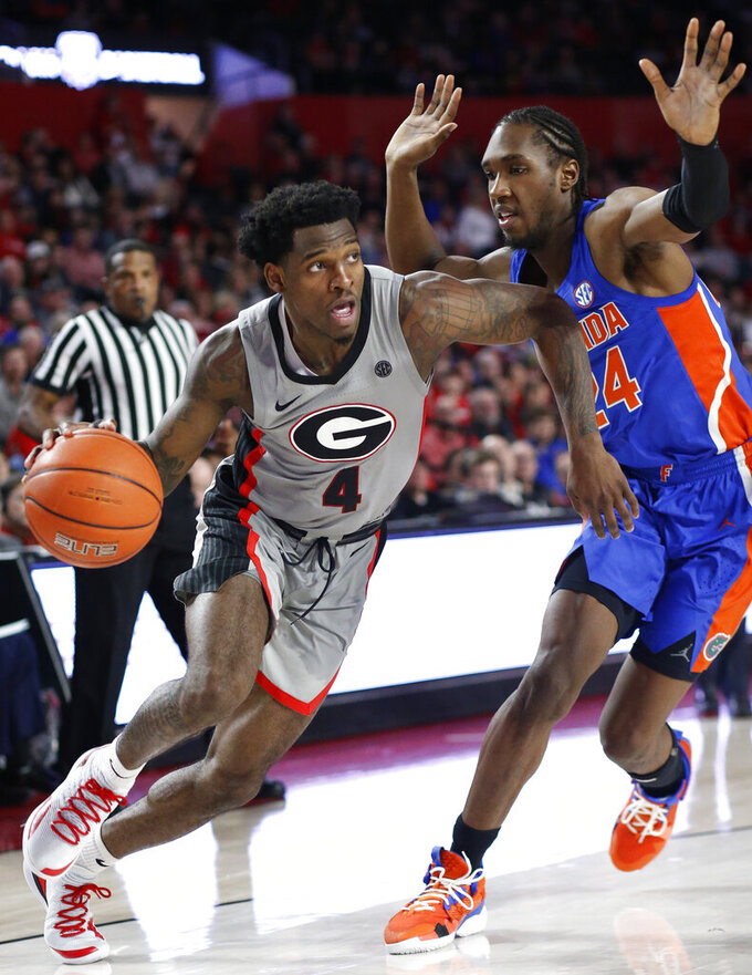 Georgia guard Tyree Crump (4) moves the ball by Florida guard Deaundrae Ballard (24) during an NCAA college basketball game in Athens, Ga., on Saturday, Jan. 19, 2019.  ( Joshua L. Jones/Athens Banner-Herald via AP)