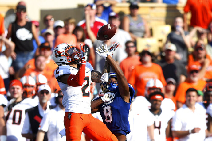 Oklahoma State wide receiver Tylan Wallace (2) makes a catch over Tulsa safety Brandon Johnson (8) during an NCAA college football game Saturday, Sept. 14, 2019, in Tulsa, Okla. (Ian Maule/Tulsa World via AP)