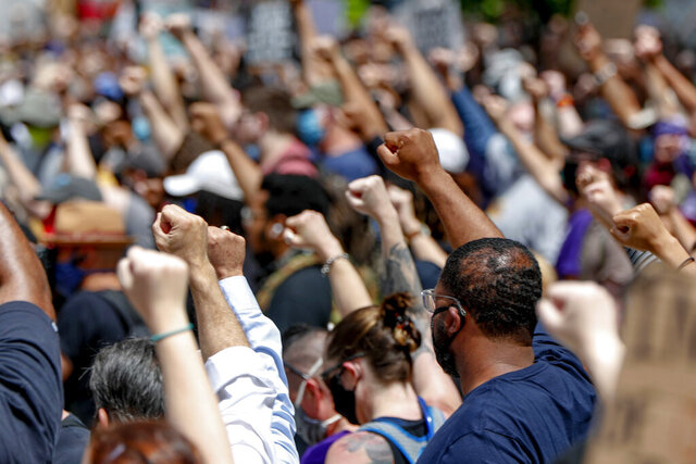 FILE - In this Saturday, May 30, 2020, file photo, demonstrators raise fists in the air during a march in Pittsburgh to protest the death of George Floyd, who died after being restrained by Minneapolis police officers on May 25. A black reporter from the Pittsburgh Post-Gazette was pulled from covering the city's protests over the death of George Floyd, apparently because of a tweet. (AP Photo/Keith Srakocic, File)