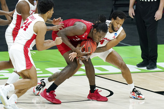 Rutgers' Cliff Omoruyi, center, and Houston's Justin Gorham, right, battle for the ball during the first half of a college basketball game in the second round of the NCAA tournament at Lucas Oil Stadium in Indianapolis Sunday, March 21, 2021. (AP Photo/Mark Humphrey)