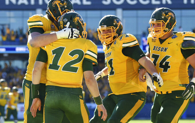 North Dakota State quarterback Easton Stick (12) is congratulated by offensive tackle Zack Johnson, left, offensive guard Luke Bacon (71), and center Tanner Volson (74) after running for a touchdown against Eastern Washington during the first half of the FCS championship NCAA college football game, Saturday, Jan. 5, 2019, in Frisco, Texas. (AP Photo/Jeffrey McWhorter)