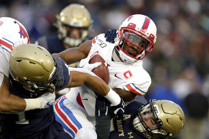 SMU wide receiver James Proche, center, is tackled by Navy linebacker Jacob Springer, left, and linebacker Diego Fagot, right, during the first half of an NCAA college football game, Saturday, Nov. 23, 2019, in Annapolis, Md. (AP Photo/Julio Cortez)