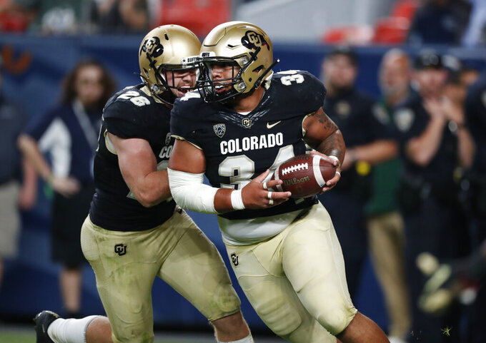 Colorado defensive end Mustafa Johnson, front, celebrates with linebacker Carson Wells after Johnson recovered a fumble and ran in or a touchdown against Colorado State in the fourth quarter of an NCAA college football game Friday, Aug. 30, 2019, in Denver. Colorado won 52-31. (AP Photo/David Zalubowski)