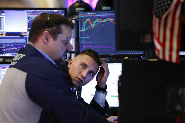 FILE - In this Jan. 15, 2020, file photo specialist Scott Vasilisin, right works with trader Michael Milano on the floor of the New York Stock Exchange. The U.S. stock market opens at 9:30 a.m. EST on Wednesday, Jan. 22. (AP Photo/Richard Drew, File)