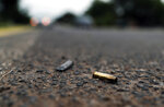 In this Oct. 16, 2019 photo spent bullet casings litter the site where a convoy of Michoacan state police were ambushed and slaughtered by Jalisco cartel gunmen, in El Aguaje, Mexico. On Monday, Oct. 14, 2019 thirteen state police officers were shot or burned to death in their vehicles on this road. (AP Photo/Marco Ugarte)