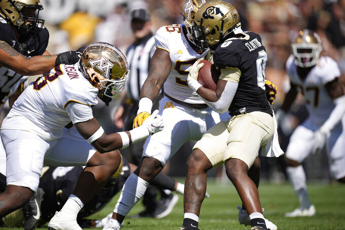 Colorado running back Ashaad Clayton, right, is stopped by Minnesota defensive linemen Val Martin, center, and MJ Anderson in the second half of an NCAA college football game Saturday, Sept. 18, 2021, in Boulder, Colo. Minnesota won 30-0. (AP Photo/David Zalubowski)