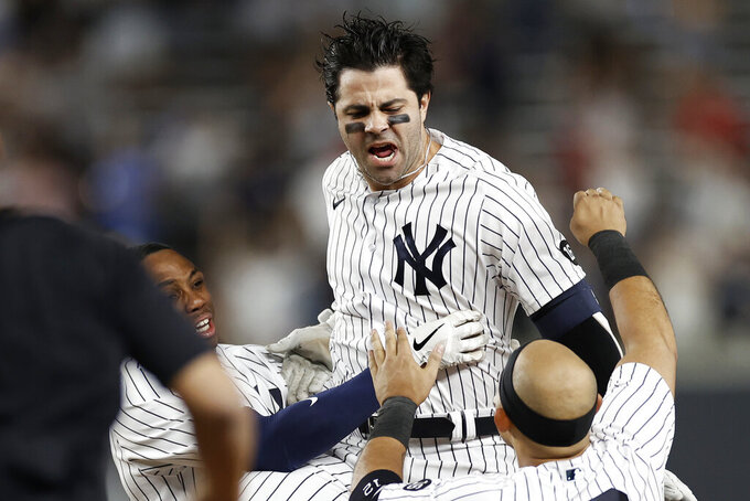 New York Yankees' Ryan LaMarre celebrates with teammates after driving in the winning run against the Philadelphia Phillies during the 10th inning of a baseball game Wednesday, July 21, 2021, in New York. The Yankees won 6-5. (AP Photo/Adam Hunger)