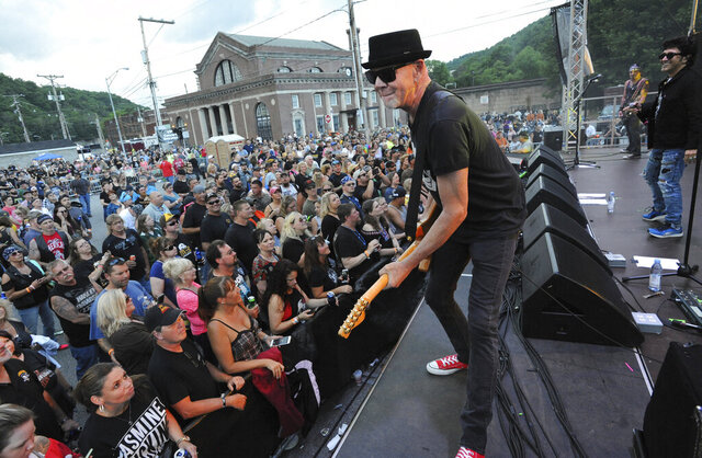 """FILE - In this June 23, 2018, file photo, Mark Kendall, center, with the band Great White, performs on the Train Station stage during the 21st Annual Thunder in the Valley motorcycle rally in Johnstown, Pa. Metal band Great White has apologized for performing at an outdoor North Dakota concert where the crowd did not wear masks despite the ongoing threat of the coronavirus. The band drew criticism on social media after the performance Thursday, July 9, 2020, as part of the """"First on First: Dickinson Summer Nights"""" concert series in Dickinson, in the southwest of the state. (John Rucosky/The Tribune-Democrat via AP, File)"""