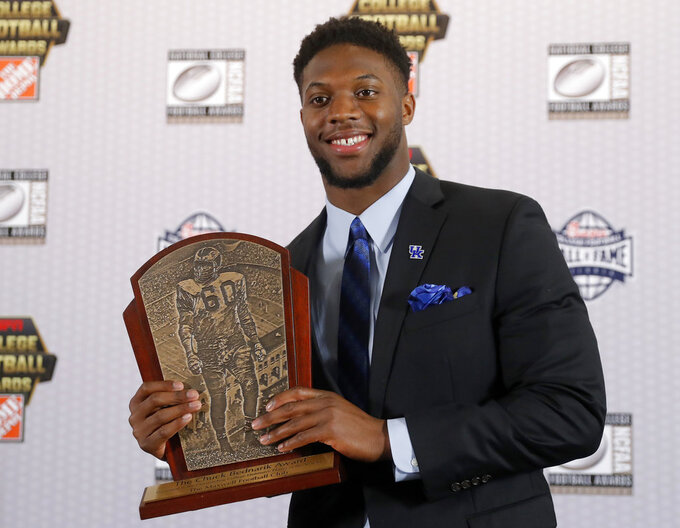 Kentucky's Josh Allen poses with the trophy after winning the Chuck Bednarik Award as college football's top defensive player of the year, Thursday, Dec. 6, 2018, in Atlanta. (AP Photo/John Bazemore)