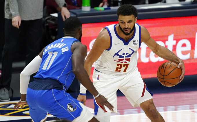 Denver Nuggets guard Jamal Murray, right, works against Dallas Mavericks forward Tim Hardaway Jr. during the first half of an NBA basketball game Saturday, March 13, 2021, in Denver. (AP Photo/David Zalubowski)