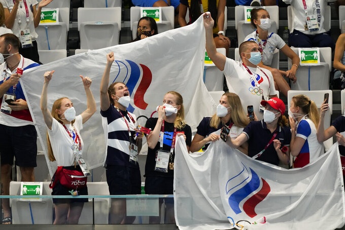 Supporters of Russian Olympic Committee team cheer Svetlana Kolesnichenko and Svetlana Romashina of Russian Olympic Committee after their competition in the Free Routine Final at the 2020 Summer Olympics, Wednesday, Aug. 4, 2021, in Tokyo, Japan. (AP Photo/Dmitri Lovetsky)