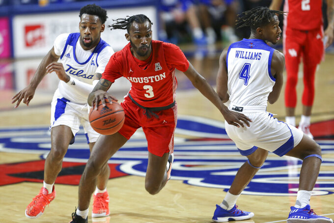 Houston's DeJon Jarreau drives around Tulsa defenders Keyshawn Embery-Simpson and Keshawn Williams during the second half of an NCAA college basketball game in Tulsa, Okla. on Tuesday, Dec. 29, 2020. Tulsa won 65-64. (AP Photo/Dave Crenshaw)
